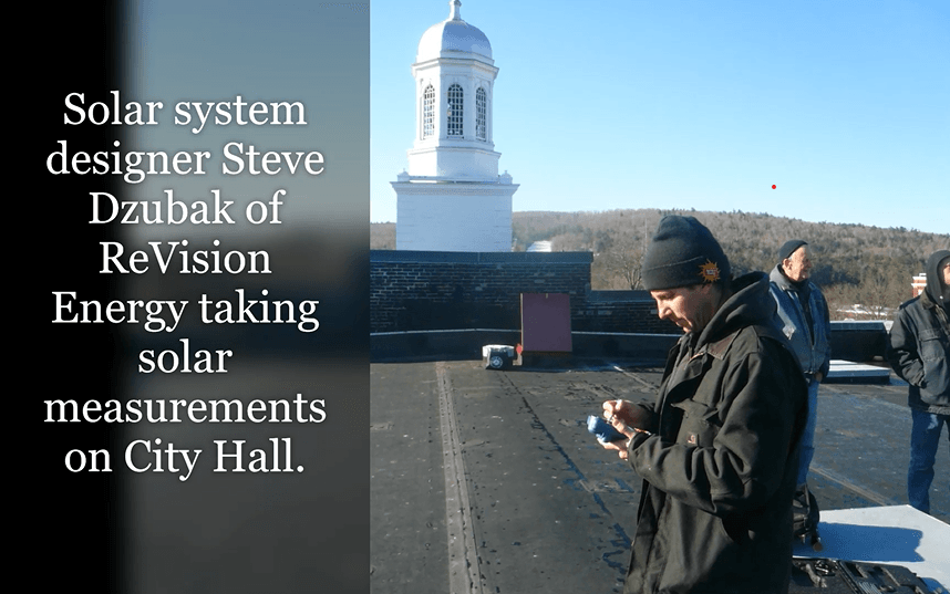 Solar system designer Steve Dzubak o ReVision Energy taking solar measurements on top of City Hall r